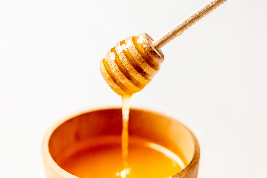 Natural bee honey in a wooden bowl on a white background
